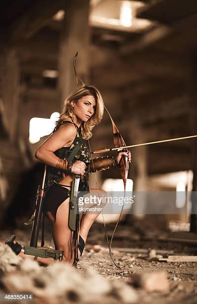 Femme tenant le tir à l'arc et prenez la Dague parmi les ruines.
