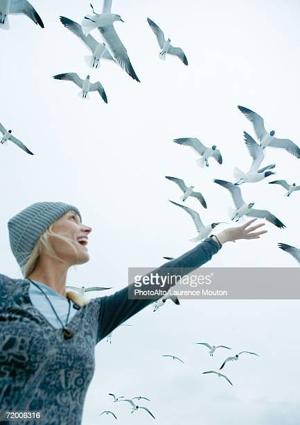 Woman holding arm up to sky where seagulls are flying