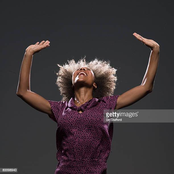 Woman holding arms in air, looking up