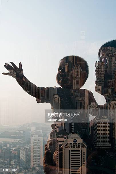 woman holding baby and cityscape double exposure