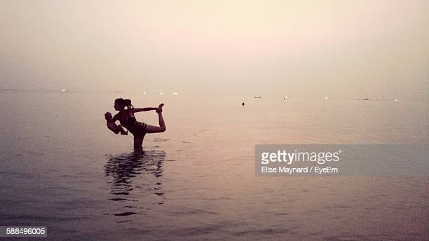 Woman Holding Baby And Doing Yoga In Water At Sea During Sunset