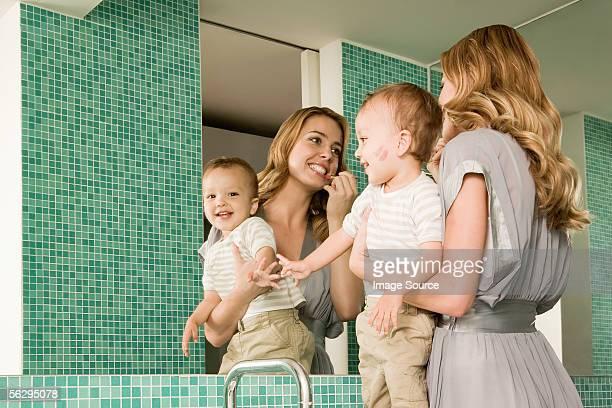 Frau holding baby und putting auf Lippenstift