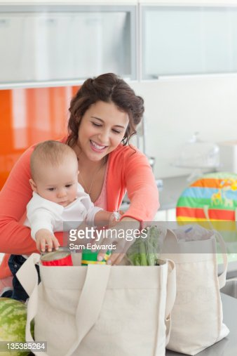 Woman holding baby and unloading groceries from reusable bag