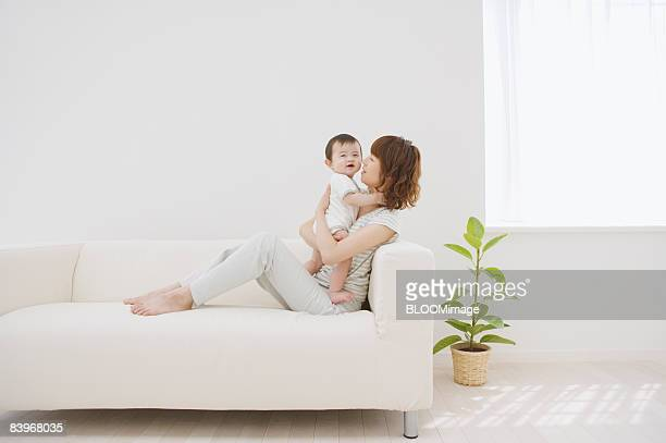 Woman holding baby on couch