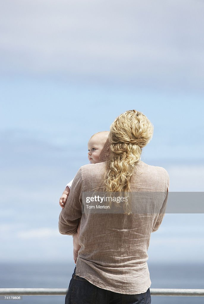 Woman holding baby outdoors : Stock Photo