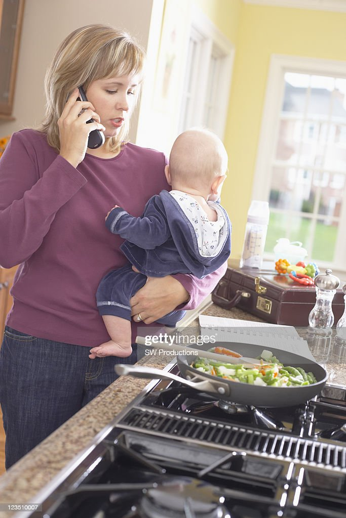 Woman holding baby while talking on the phone and cooking : Stock Photo