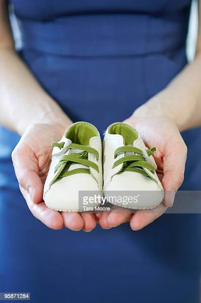woman holding baby's shoes