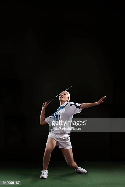Woman holding badminton racket isolated over black background