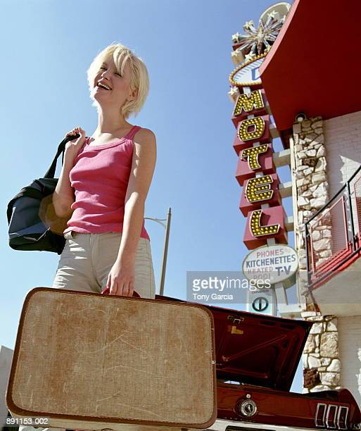 Woman holding bag and suitcase in front of motel
