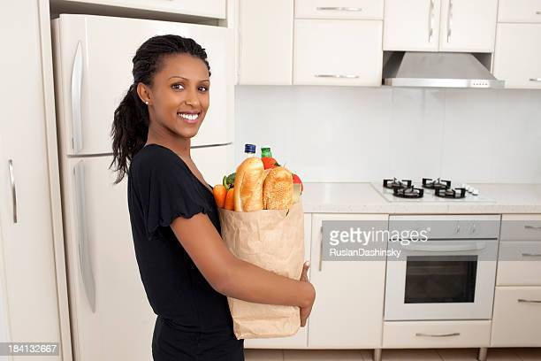 Woman holding bag with grocery products at kitchen.