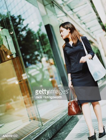 Woman holding bags, looking at window