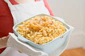 Woman holding baking dish of macaroni cheese, mid section
