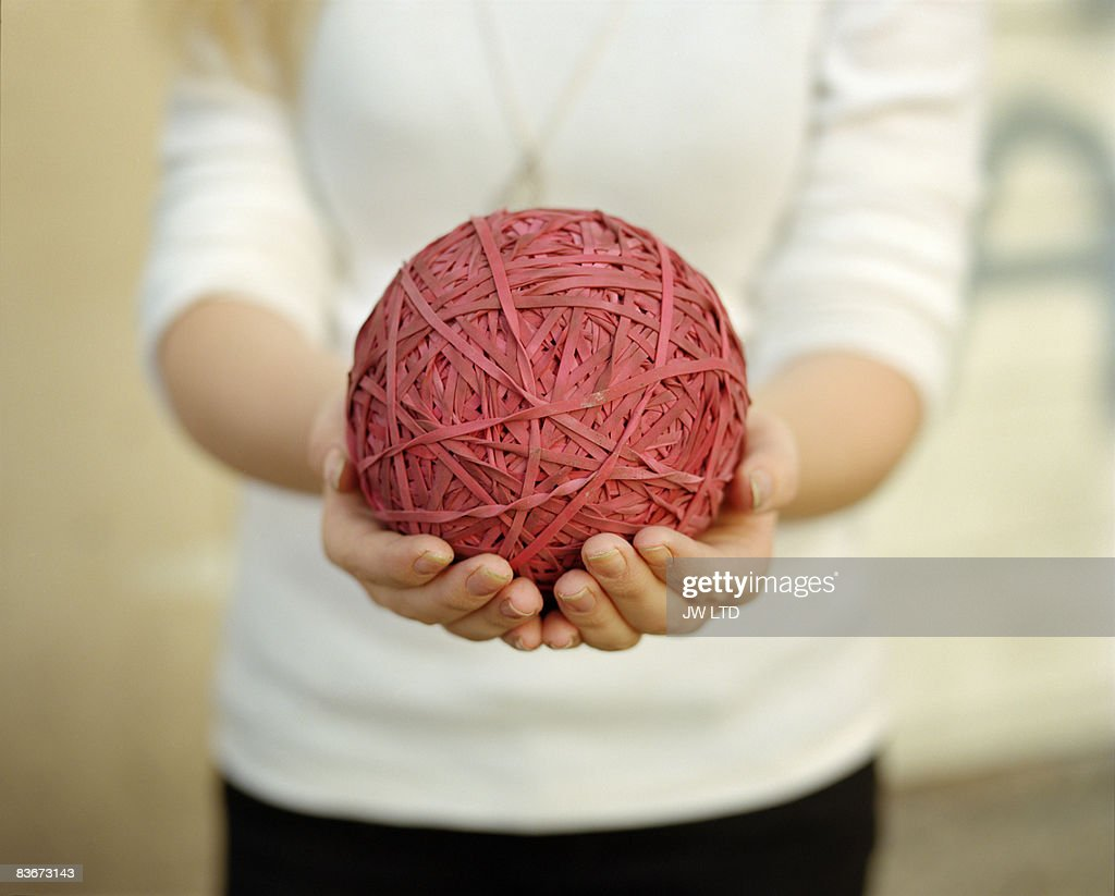 Woman holding ball of rubber bands, close up : Stock Photo