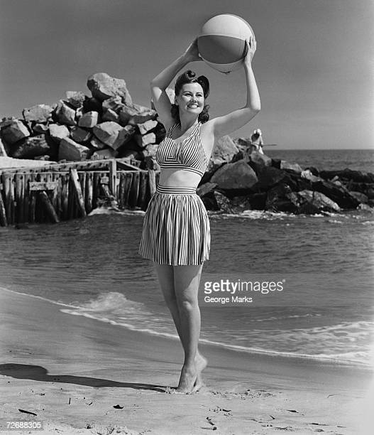 Woman holding ball on beach, (B&W)
