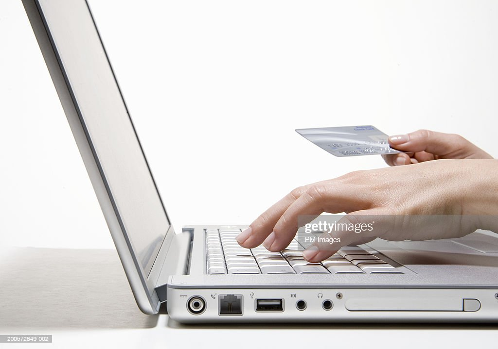 Woman holding bank card using laptop, side view, close-up : Foto de stock
