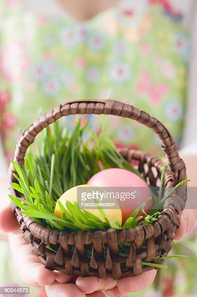 Woman holding basket of coloured Easter eggs, close-up, mid section