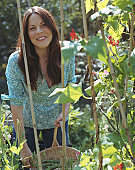 Woman holding basket of home grown vegetables, looking away, smiling