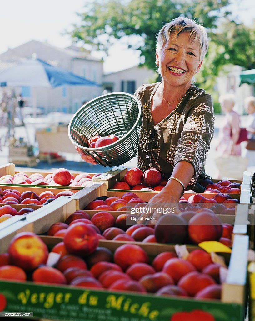 Woman holding basket of nectarines by fruit stall, smiling, portrait : Photo