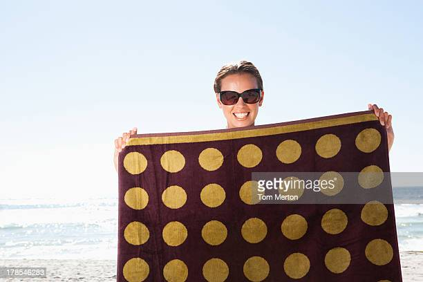 Woman holding beach towel on beach