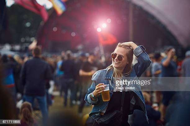 Woman holding beer and laughing at concert