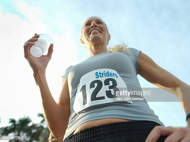 Woman holding beverage at race, smiling, low angle view