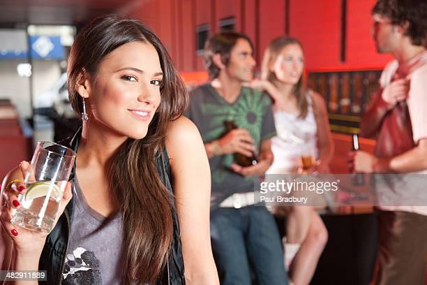 Frau hält Getränke in der Diskothek Lächeln