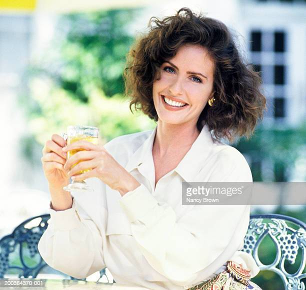 Woman holding beverage in outdoor cafe, portrait