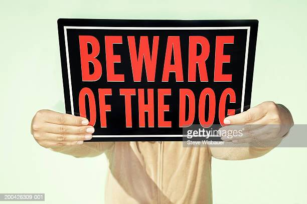 Woman holding 'Beware of Dog' sign