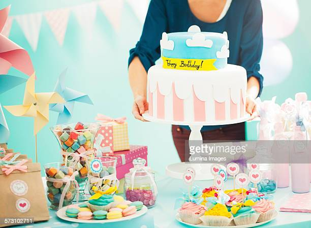 Woman holding birthday cake at party