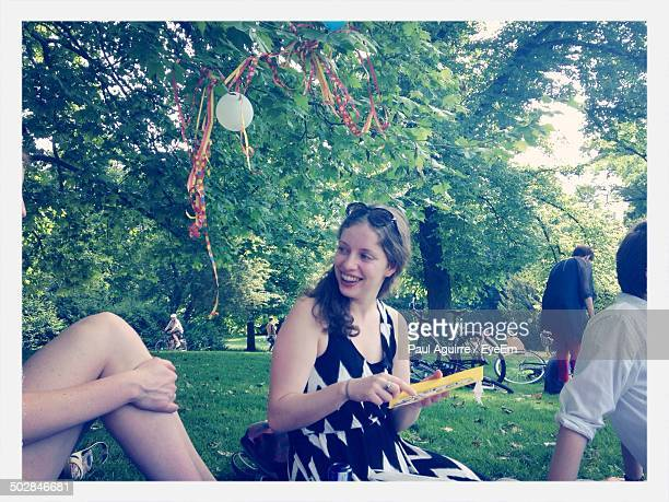 Woman holding birthday card while looking at friend in park