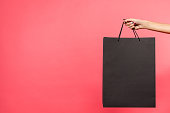cropped shot of woman holding black shopping bag isolated on red