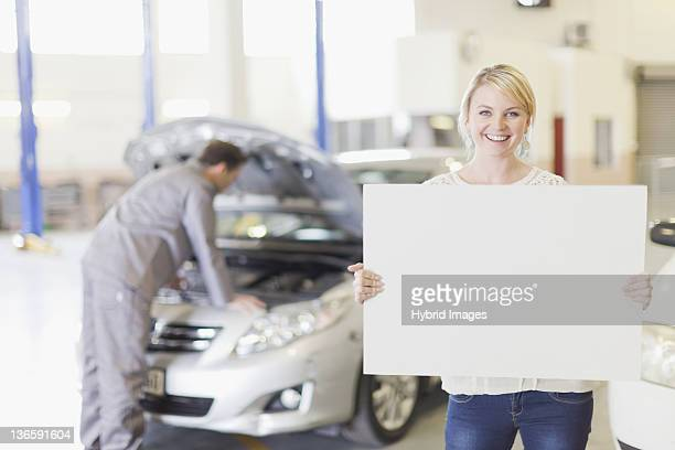 Woman holding blank card in garage