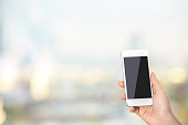 Woman's hand holding blank smartphone on blurry background with copy space. Mock up