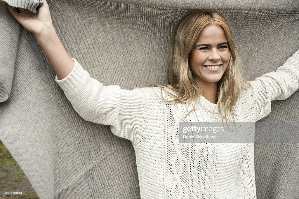 Woman holding blanket over head