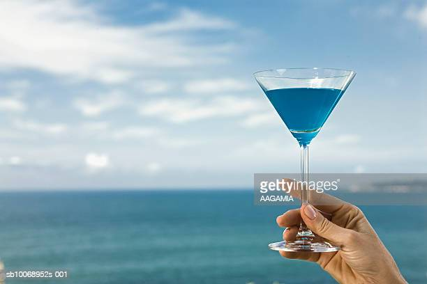 Woman holding blue cocktail against seascape, close-up of hand