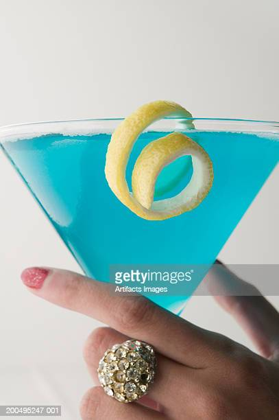 Woman holding blue martini, close-up
