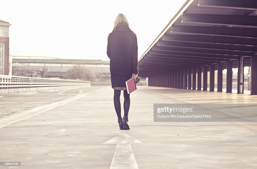 Woman holding book on city street
