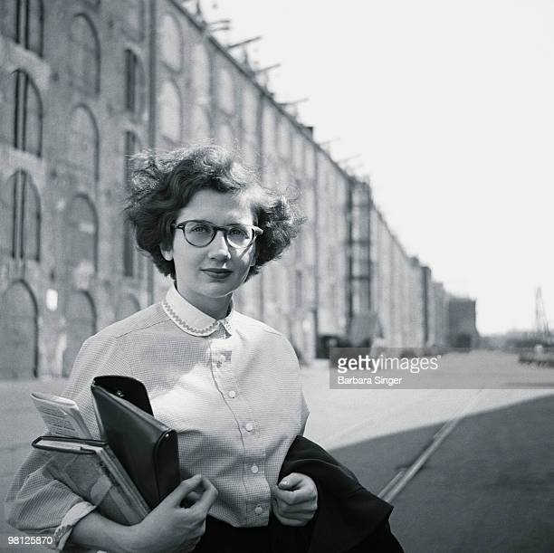 Woman holding books by warehouse