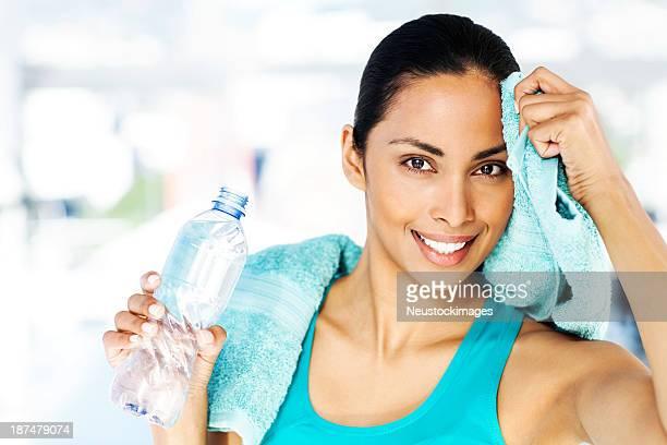 ボトルを持つ女性のクリーニングから額の「Sweat (スウェット)」ジム