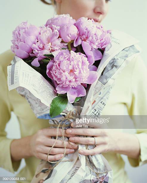 Woman holding bouquet of peonies wrapped in newspaper