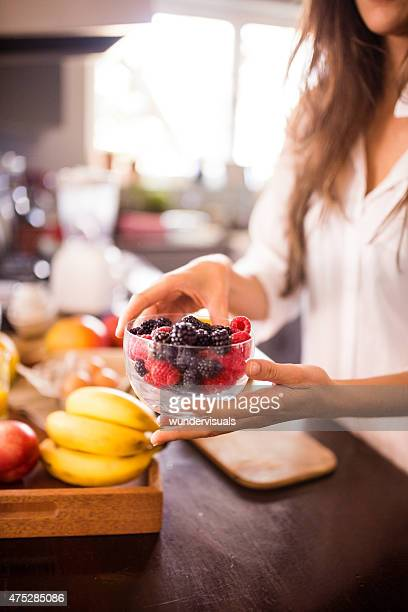 Woman holding bowl of fresh berries for a healthy breakfast