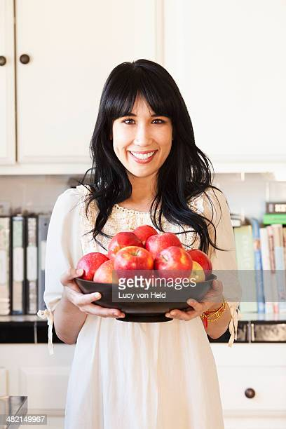 Woman holding bowl of fruit in kitchen