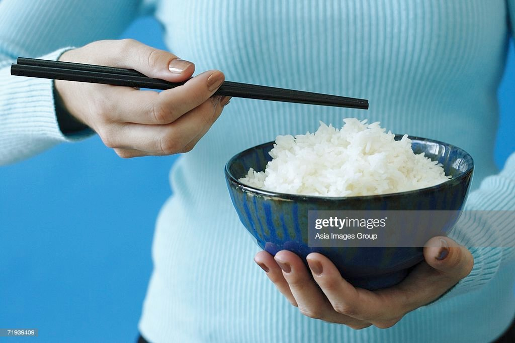 Woman holding bowl of rice and chopstick : Stock Photo