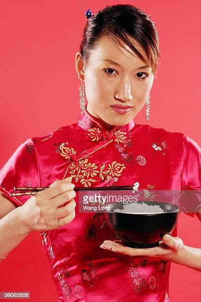 Woman holding bowl of rice and chopsticks, looking at camera