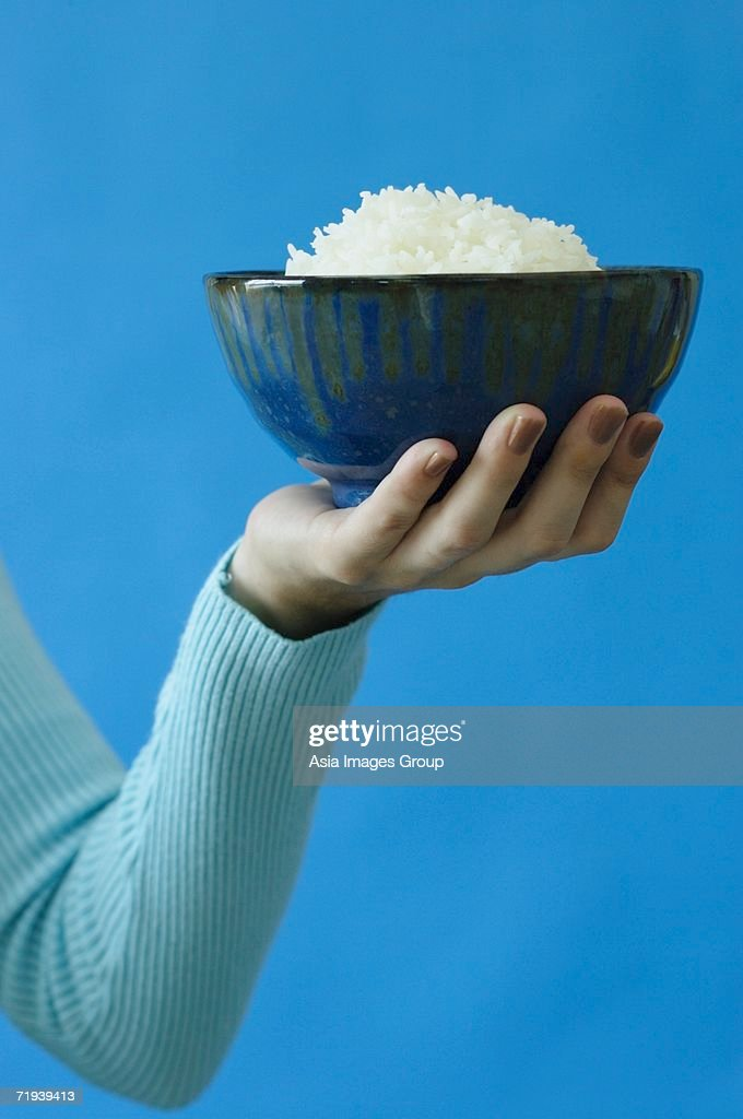 Woman holding bowl of rice in one hand : Stock Photo