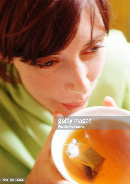 Woman holding bowl of tea, close-up