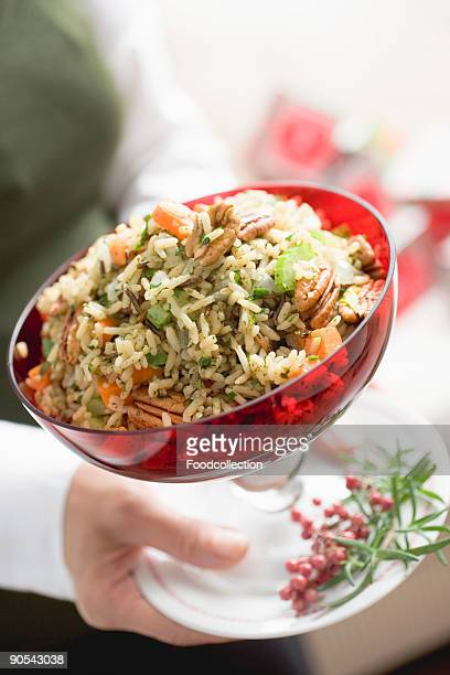 Woman holding bowl of vegetable rice with pecans, mid section