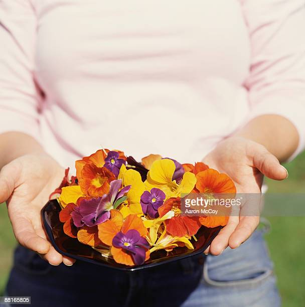 Woman holding bowlful of flower petals