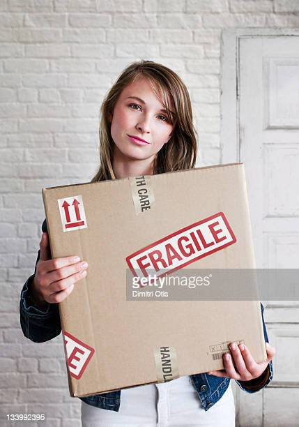 Woman holding box of fragile goods, smiling