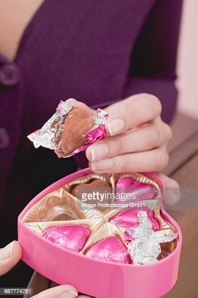 Woman holding box of heart-shaped chocolates & single chocolate